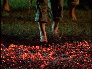 Man walking barefoot over hot coals